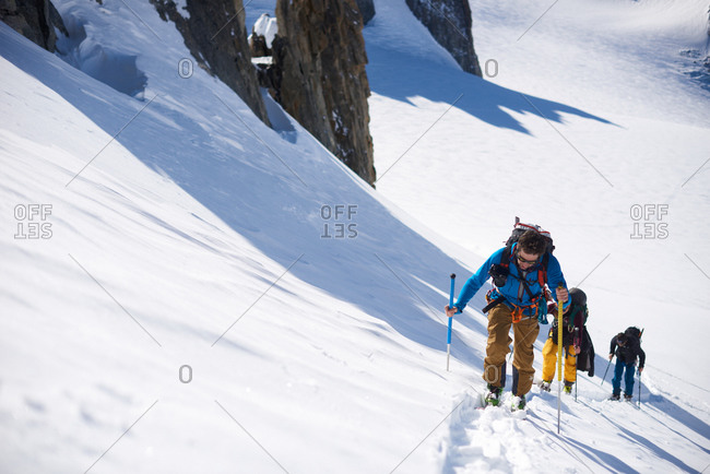 Group of 3 people ski touring up hill
