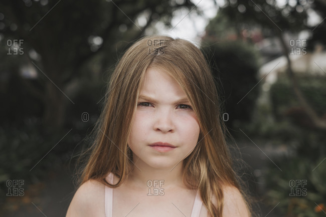 Portrait of a young girl with a serious face standing outside