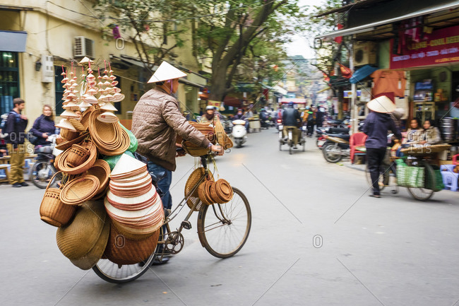 Hanoi, Vietnam - February 6, 2015: Man on bicycle selling hats in Old Quarter, Hanoi, Vietnam