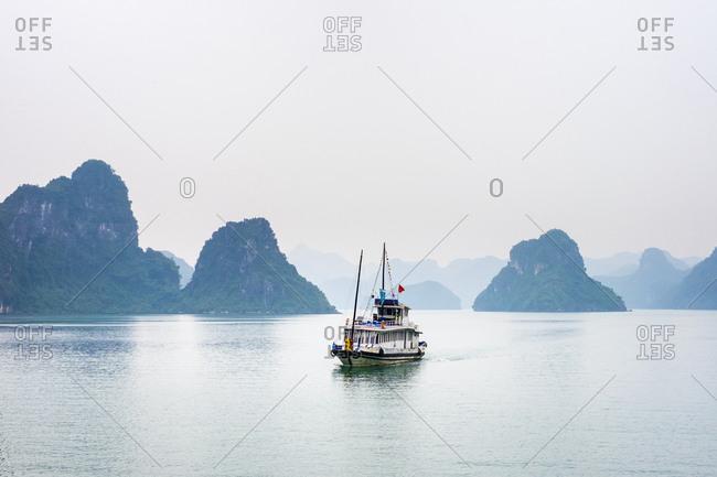 Ha Long, Quang Ninh, Vietnam - February 9, 2015: Boat passes through foggy karst landscape in Ha Long Bay, Vietnam
