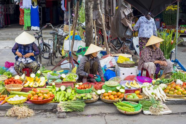 Hoi An, Quang Nam Province, Vietnam - February 28, 2015: Women selling vegetables at market, Hoi An, Vietnam