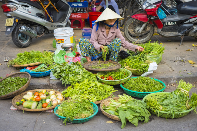 Hoi An, Quang Nam Province, Vietnam - March 2, 2015: Woman selling vegetables at street market, Hoi An, Vietnam