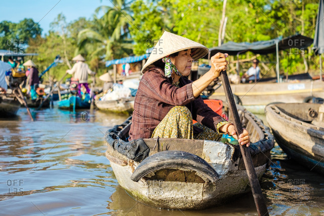Can Tho, Vietnam - March 28, 2015: A Vietnamese woman paddles a boat at Phong Dien Floating Market, Can Tho, Vietnam