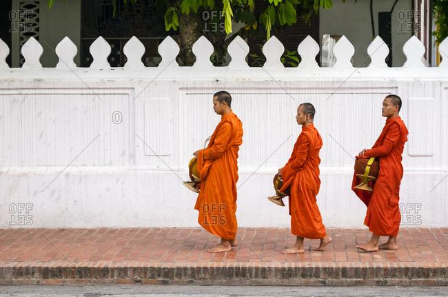 Luang Prabang, Luang Prabang Province, Laos - May 16, 2015: Buddhist novice monks receive alms (Tak Bat), Luang Prabang, Laos