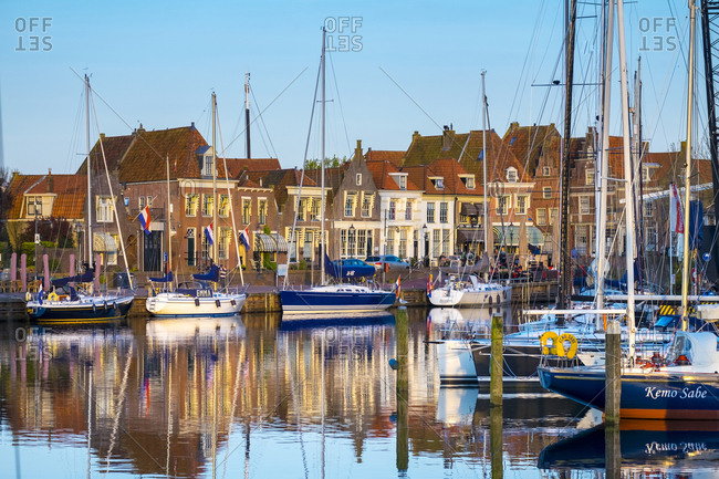 Enkhuizen, North Holland, Netherlands - May 4, 2016: Boats moored in front of historic buildings along the Oude Haven (Old Harbor), Enhuizen, North Holland, Netherlands