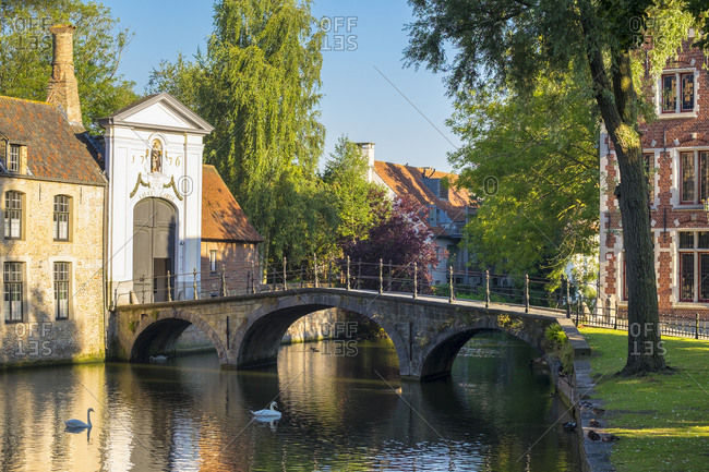 Bruges, Flanders, Belgium - August 15, 2016: Wijngaard Bridge and the main entrance gate of the Begijnhof, Bruges, West Flanders, Belgium