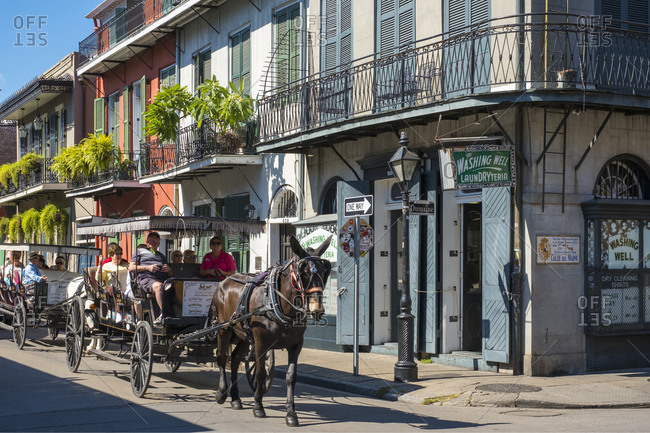 New Orleans, Louisiana, United States - October 13, 2016: Horse-drawn carriage and buildings on Bourbon St., New Orleans, Louisiana, United States
