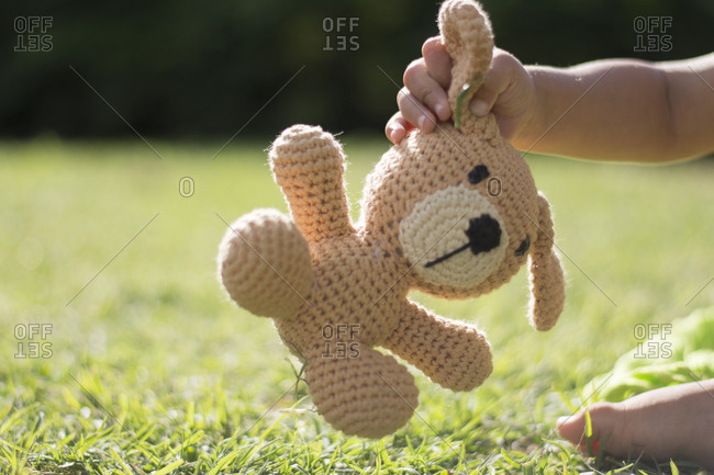 Boy holding his stuffed animal in the park