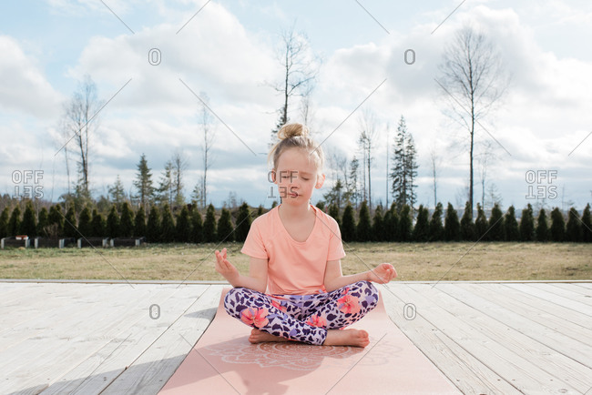 young girl meditating doing yoga in her back yard at home