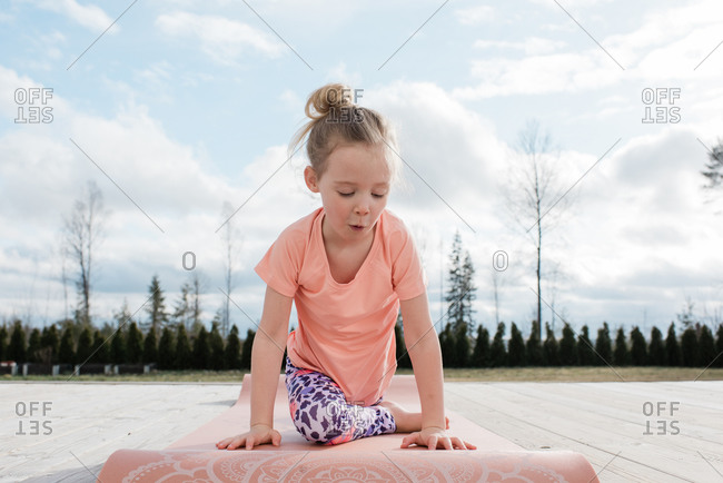 young girl doing yoga stretching in her back yard at home