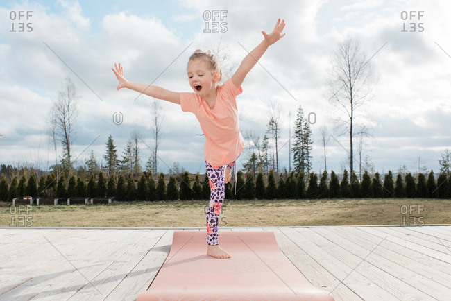 young girl balancing on a yoga mat in her back yard at home
