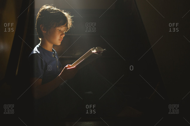 A boy sits on a darkened staircase in a bright beam of light reading