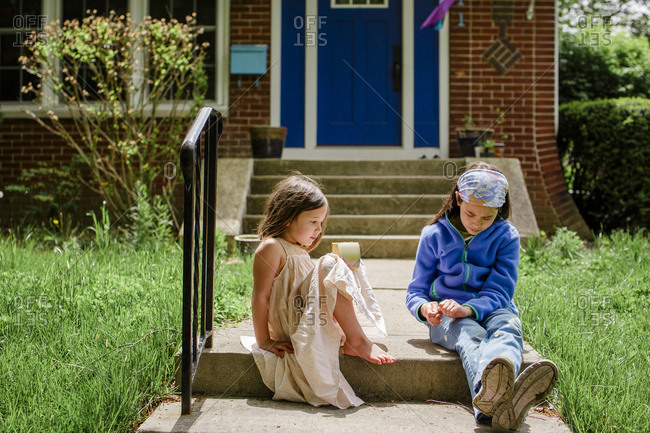 Two little girls sit on front stoop in sunshine talking to each other
