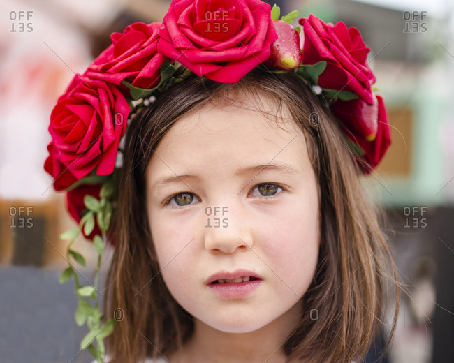 Portrait of a serious little girl with a wreath of roses in her hair