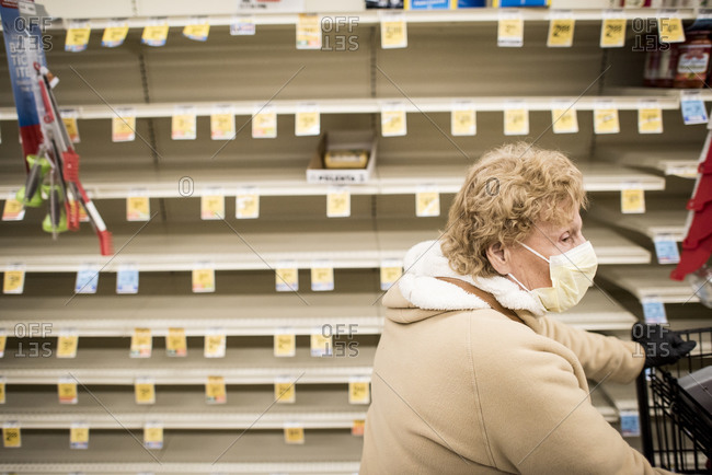 San Diego, California, United States - March 13, 2020: A woman with a face mask walks past empty shelves in a supermarket.