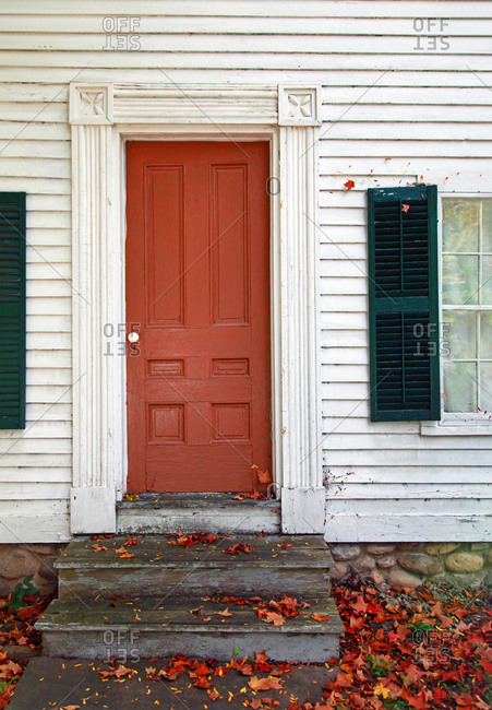 Colonial Home with Orange Door in the Fall Season
