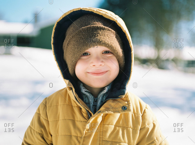 A happy little boy smiling over the snow in his backyard.