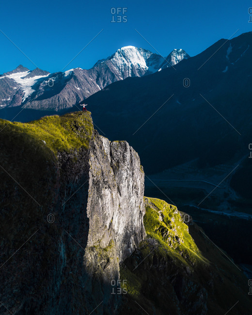 Aerial view of a man on the top of bright side of rocks in the evening with snow peaks on the background, Kabardino-Balkaria, Russia.