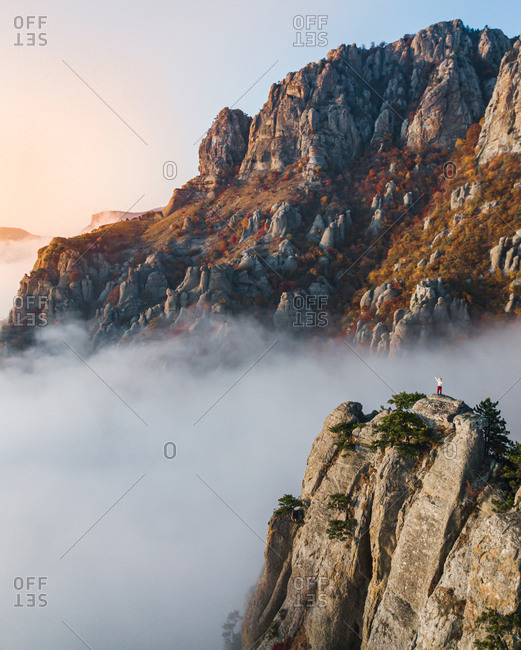 Aerial view of a man standing on the rocks infront of mount Demerdzhi with colored trees amongst the mist at sunset time, Crimea, Russia.