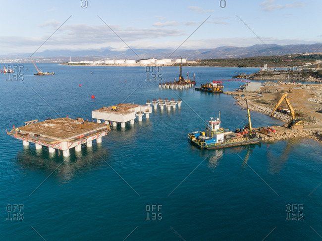 Aerial view of machinery at the construction of future LNG terminal on the shore of the bay in Omisalj, Croatia
