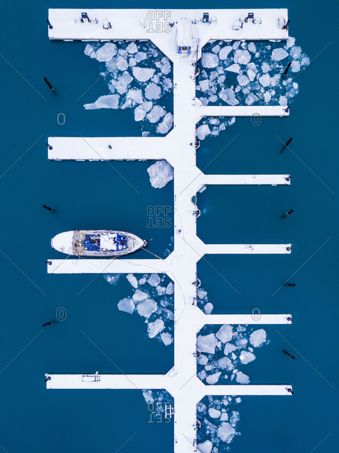 Aerial view above of single boat anchored at the frozen pier, United States.