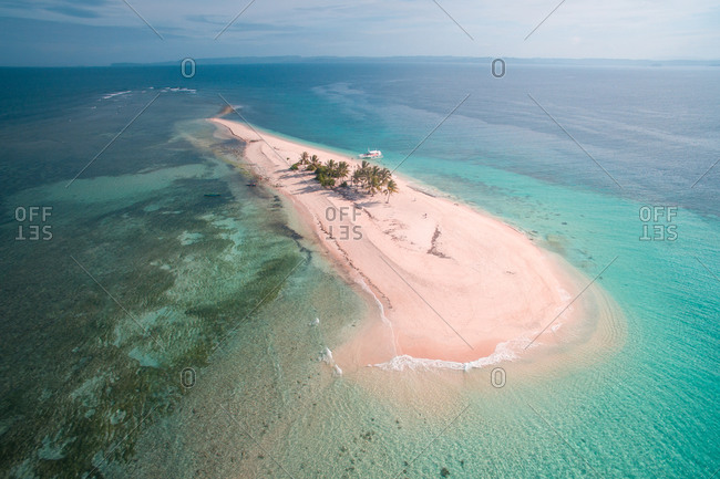 Aerial view of a beautiful virgin white-sand beach and crystal-clear waters of Hagonoy Island Beach in San Agustin, Surigao del Sur, Philippines