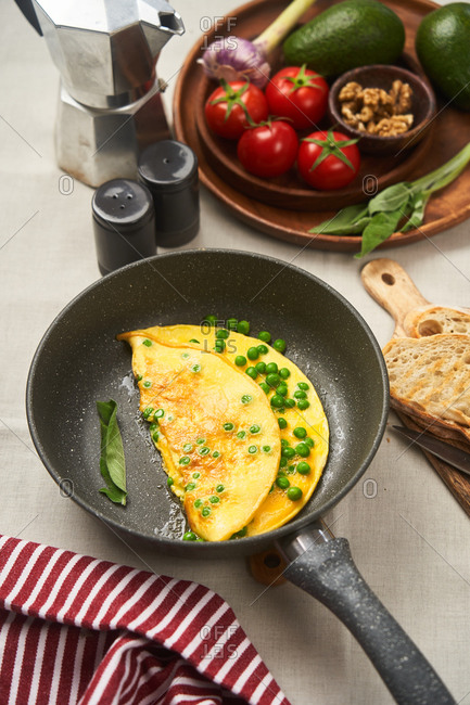 Omelet with peas in a skillet