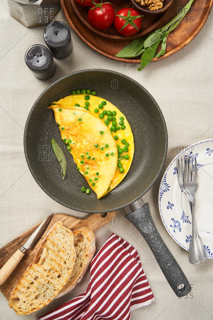 Overhead view of an omelet with peas in a skillet
