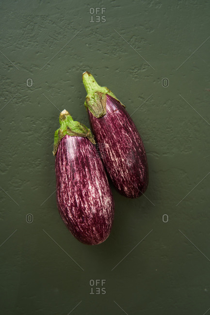 Eggplants on green textured background