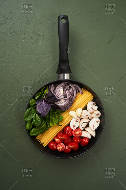 Pasta ingredients in a pan on green textured surface