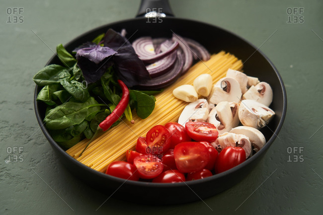 Close up of pasta ingredients in a pan on green textured surface