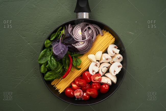 Top view of pasta ingredients in a pan on green textured surface