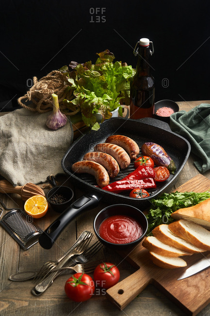 Sausage and fresh veggies in a skillet on rustic table