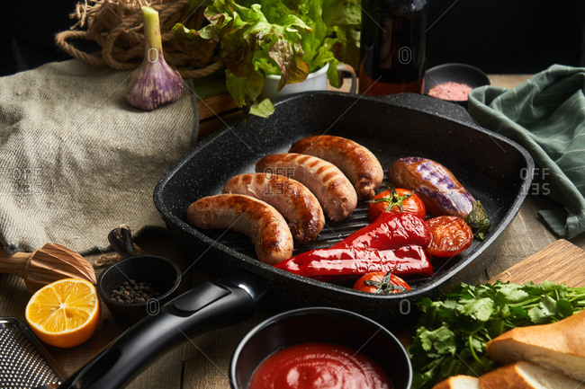 Close up of sausage and fresh veggies in a skillet on rustic table