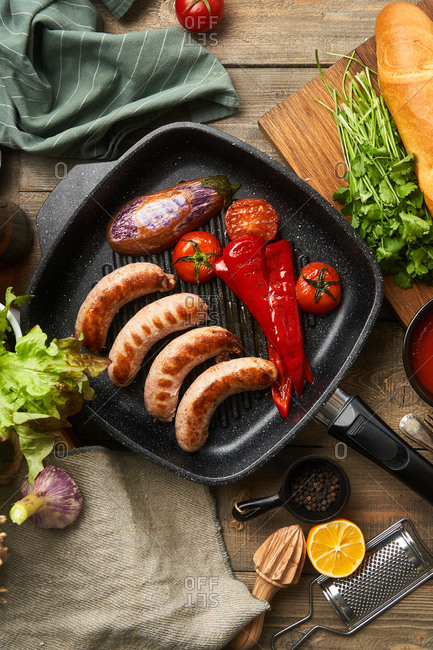 Top view of sausage and fresh veggies in a skillet on rustic table