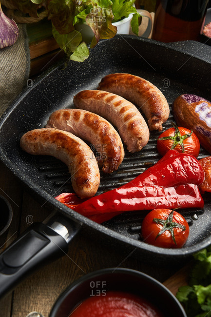 Sausage and fresh peppers, tomatoes and eggplant in a skillet