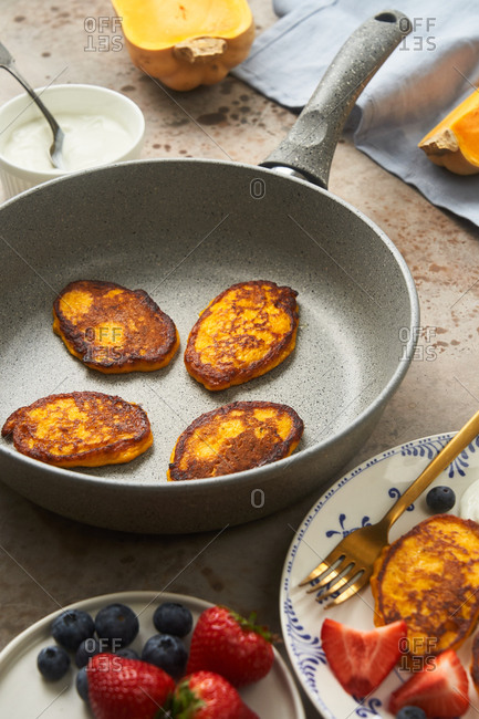 Butternut squash pancakes in a skillet on kitchen counter