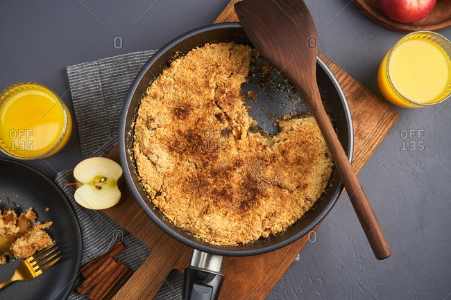 Overhead view of apple crumble in a skillet being served