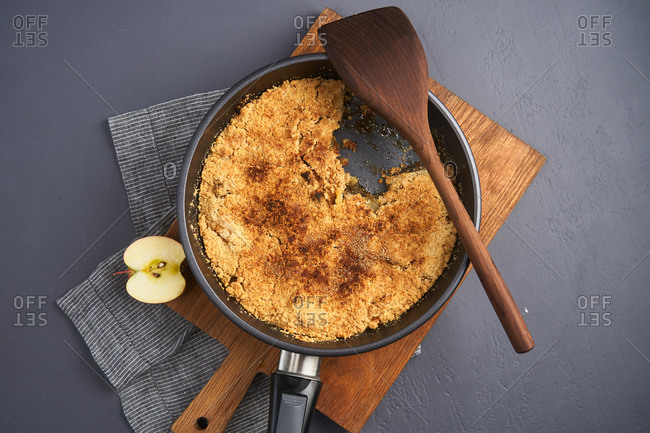 Top view of apple crumble in a skillet being served