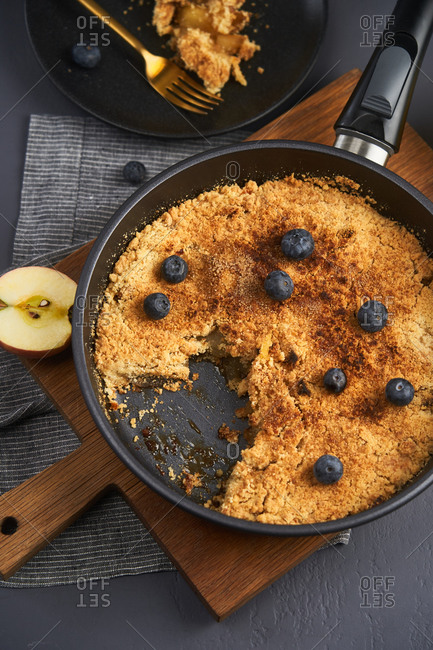 Top view of apple crumble in a skillet topped with blueberries