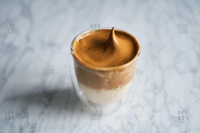Close up of Dalgona whipped coffee on light background