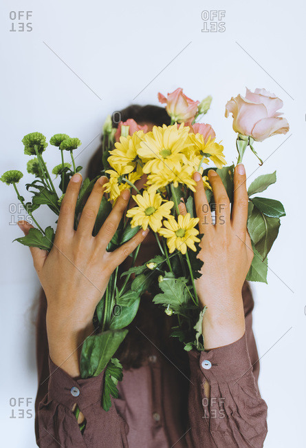 Woman holding a variety of spring flowers in her sleeves