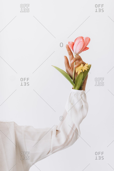 Woman holding pink and yellow flowers in her sleeve