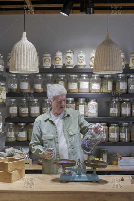 Senior man behind the counter in his shop holding jar of dried lavender blossoms