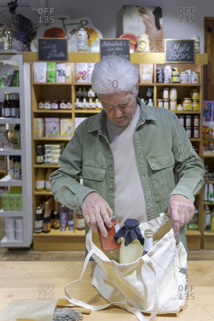 Senior man buying groceries in a small food store