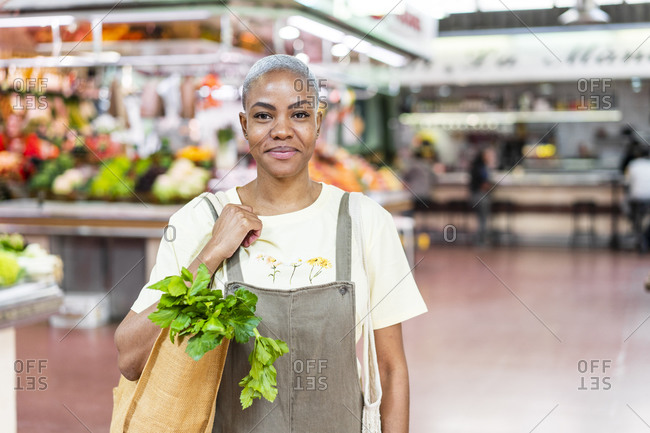 Portrait of smiling woman buying groceries in a market hall