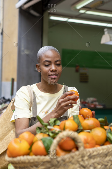 Woman buying tangerines in a market hall