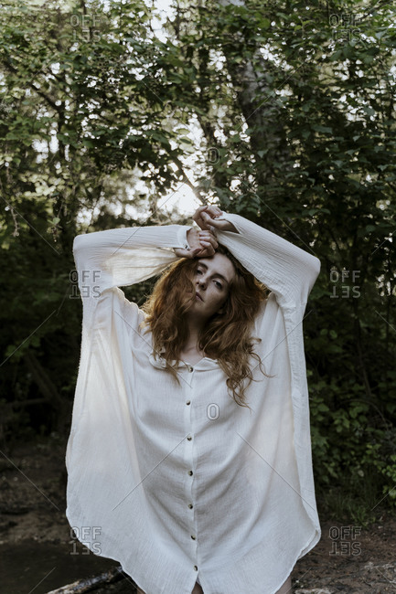 Young redhaired woman wearing baggy shirt in forest