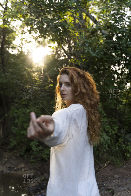 Young red-haired woman reaching out her hands in the forest