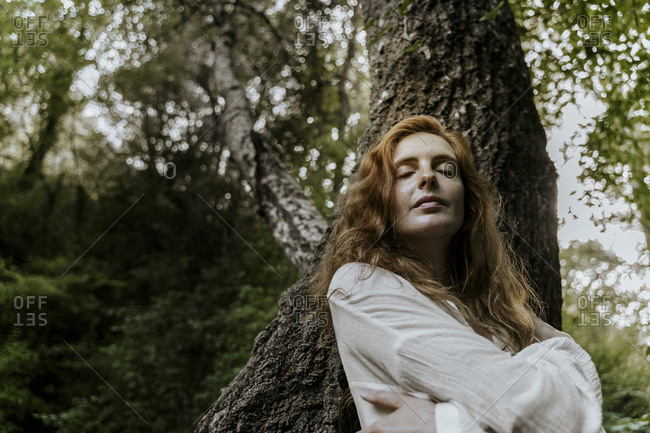Young redhaired woman with closed eyes leaning on tree trunk